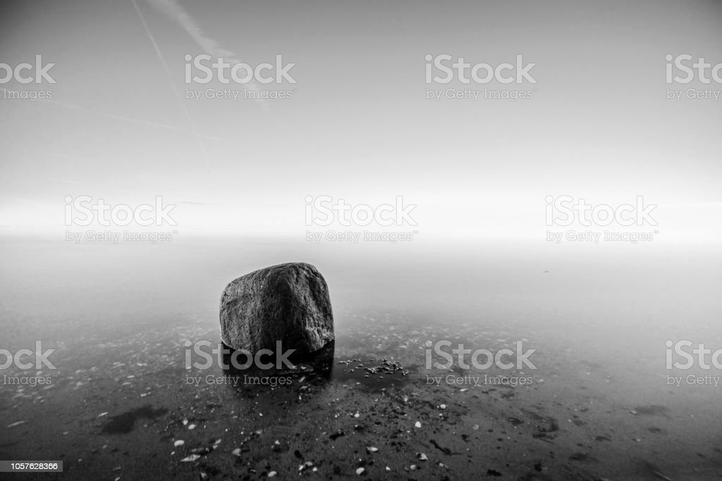 Single rock in the water by the sea stock photo