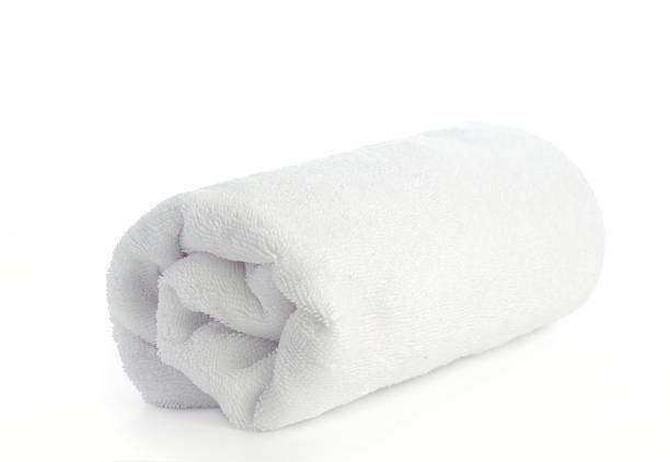 Single rolled up white beach towel on a white surface stock photo