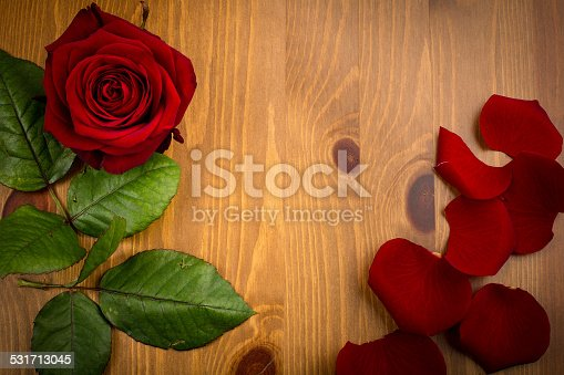 A single red love rose with petals and leaf on a wooden background like a frame with copy space.
