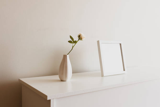 Single rose in small vase next to blank square picture frame stock photo