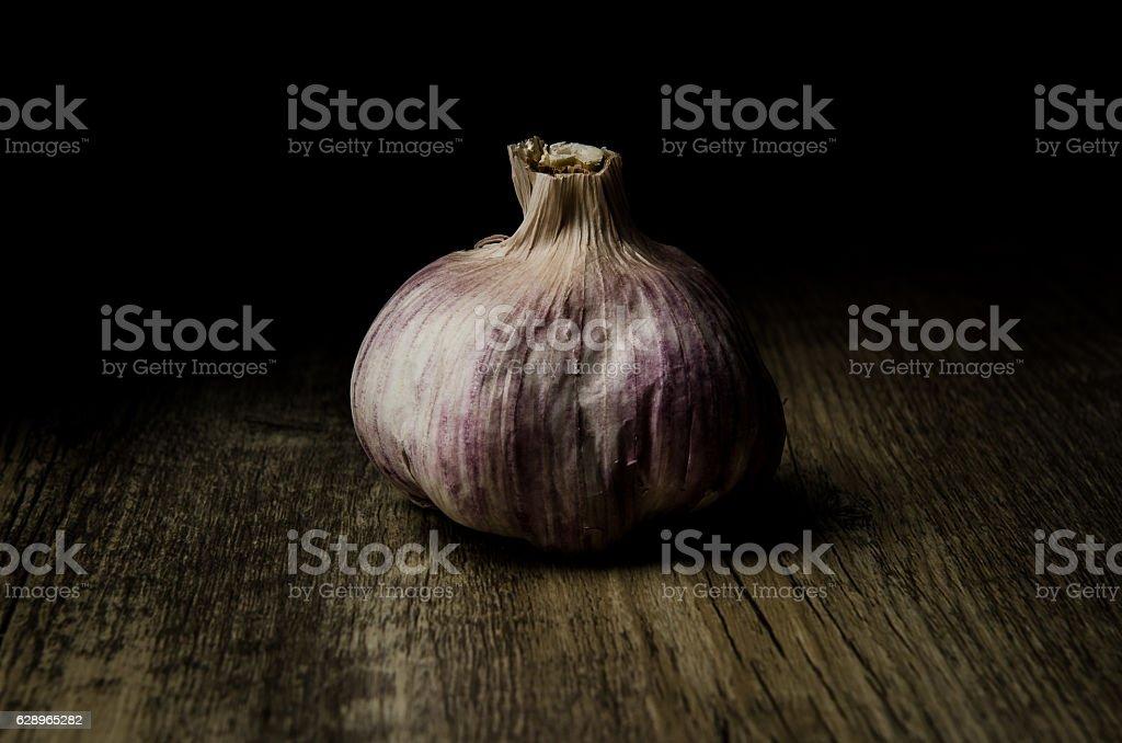 Single rustic  garlic on wood stock photo