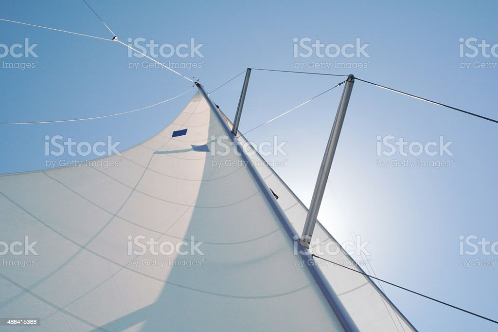 single sail with the sun behind it, connected to the mast stock photo