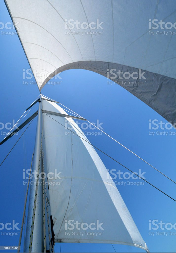 single sail with the sun behind it stock photo