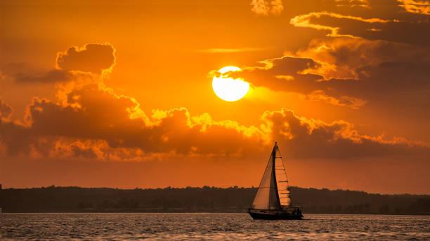 Single sailboat at sunset stock photo