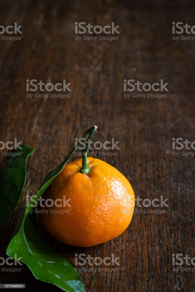 Single Satsuma Mandarin on an Wooden Table with Copy Space stock photo