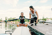 Single scull rowing. 12 years girl rowing single scull. She is preparing for new competitions. Rowing on Sava river. Coach giving instructions to girl rowing. Her mother is her coach.