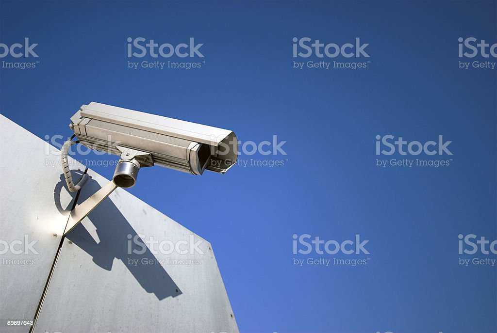 A single security camera against a blue sky royalty-free stock photo