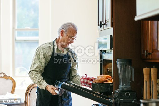istock Single senior man cooking turkey 617897978