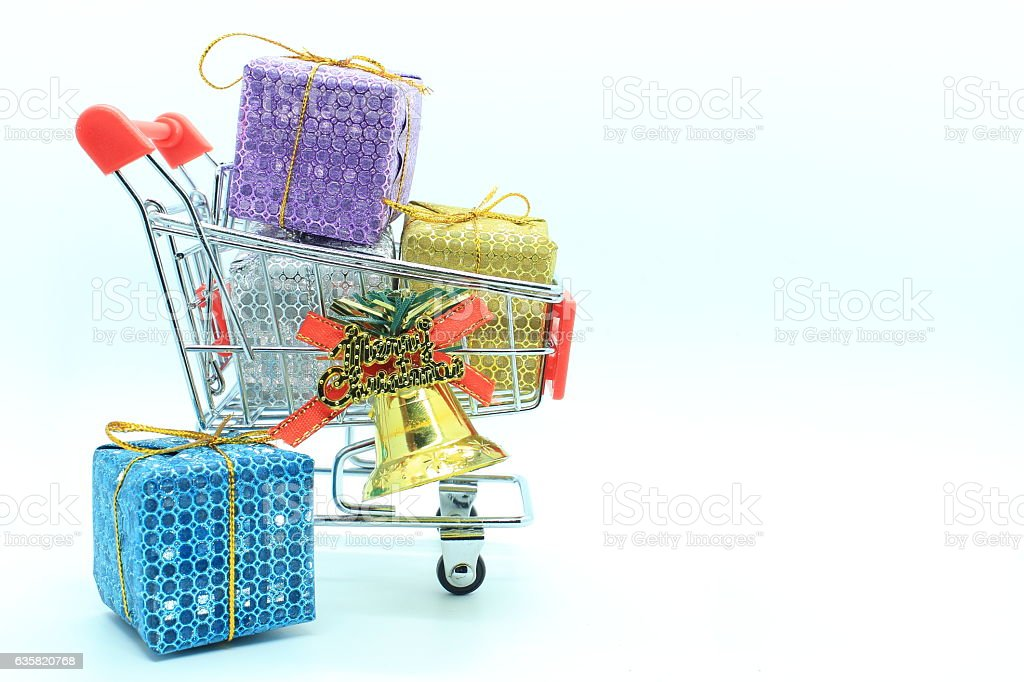 single shopping cart with four gift boxs and golden bell. stock photo