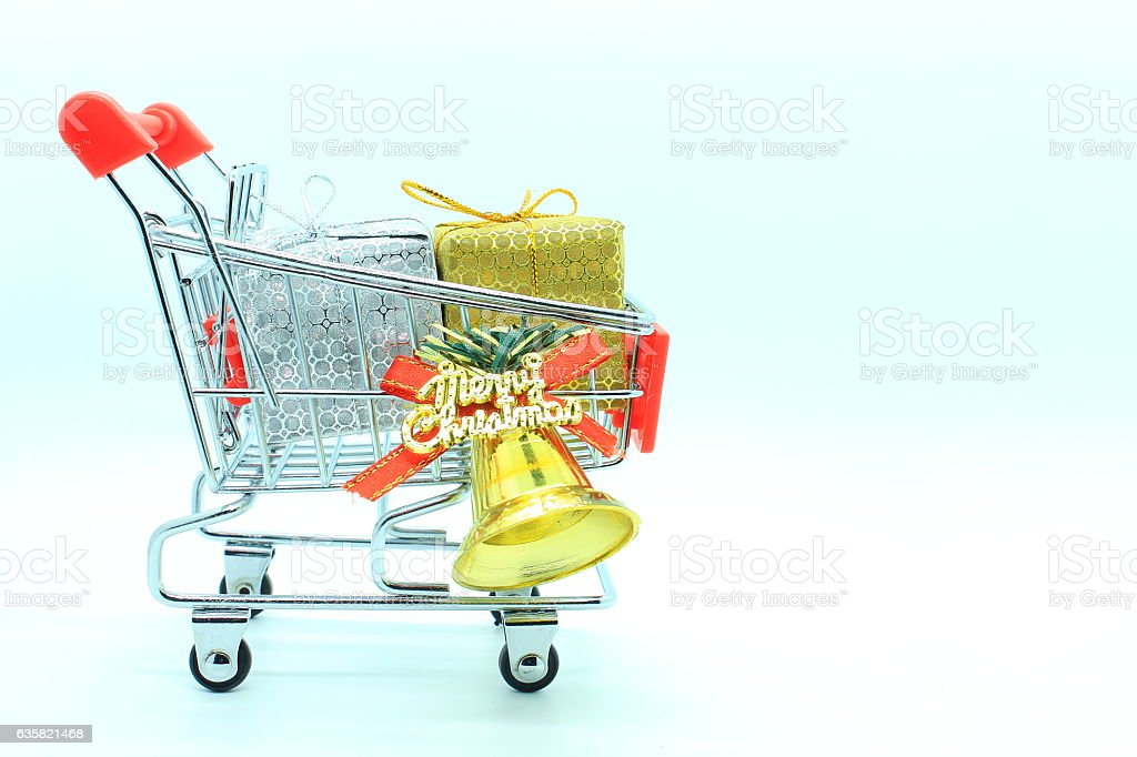 single shopping cart with two gift boxs and golden bell. stock photo