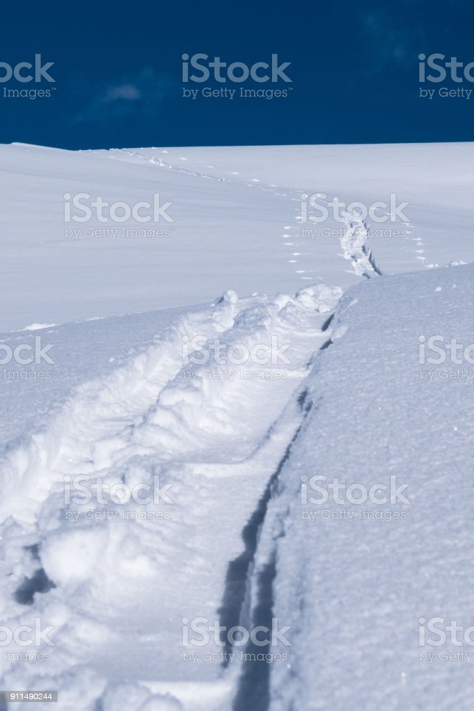A single skier touring track imprint in new powder snow stock photo