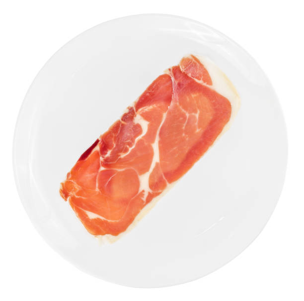 Single slice of raw prosciutto crudo or jamon on white plate isolated stock photo