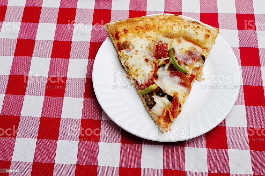 Single Slice Supreme Pizza on Red Gingham royalty-free stock photo