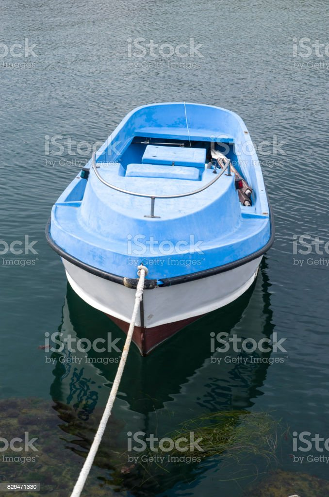 Single small plastic rowing boat in port stock photo