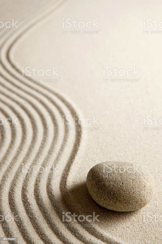 Single smooth stone next to wavy lines on a white surface stock photo