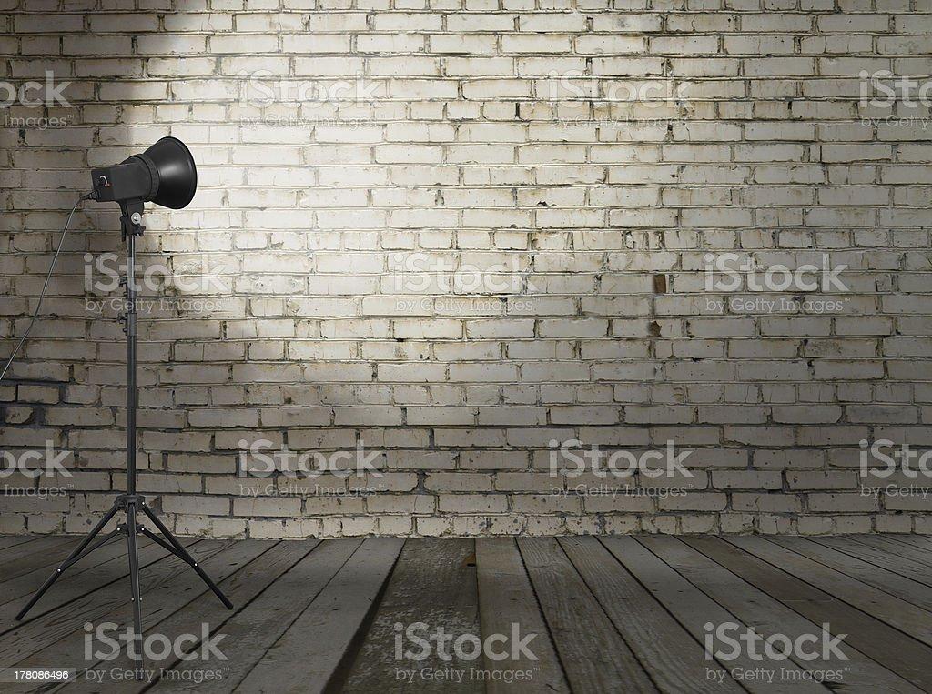 Single spotlight in brick walled studio royalty-free stock photo
