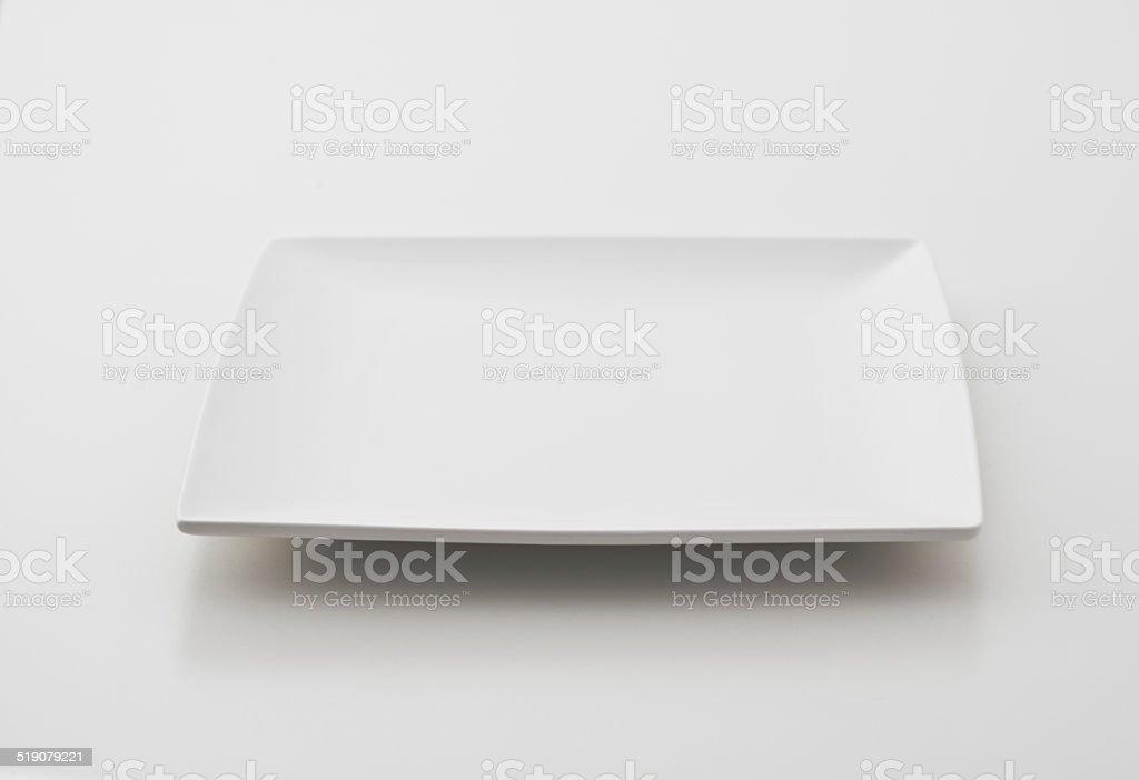 Single square porcelain plate on white background stock photo