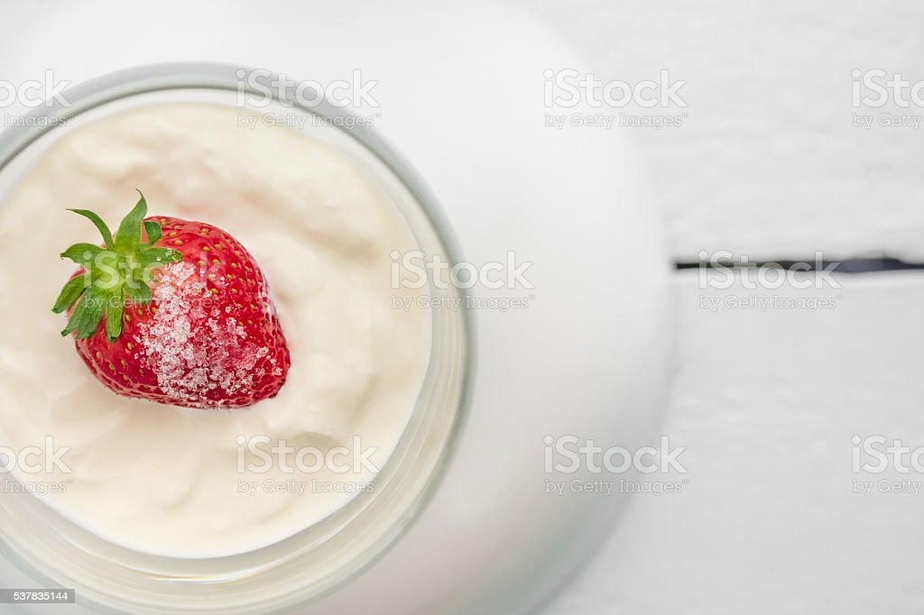 Single strawberry with sugar, cream or yogurt – zdjęcie