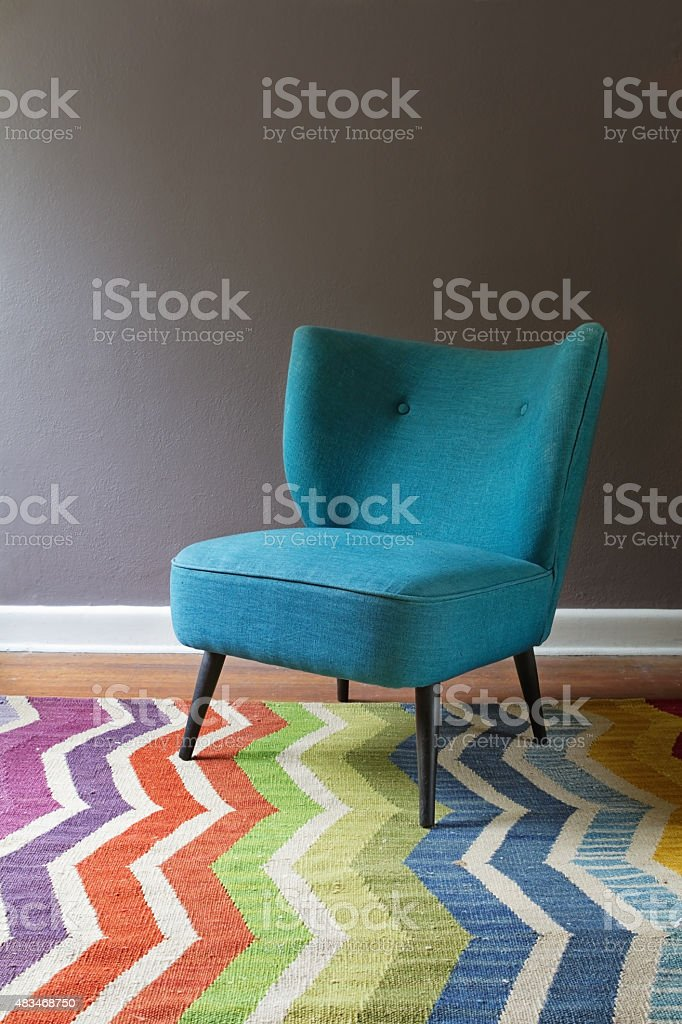 Single teal blue armchair and colorful chevron pattern rug interior stock photo