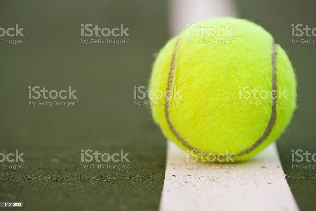 A single tennis ball on a court royalty-free stock photo