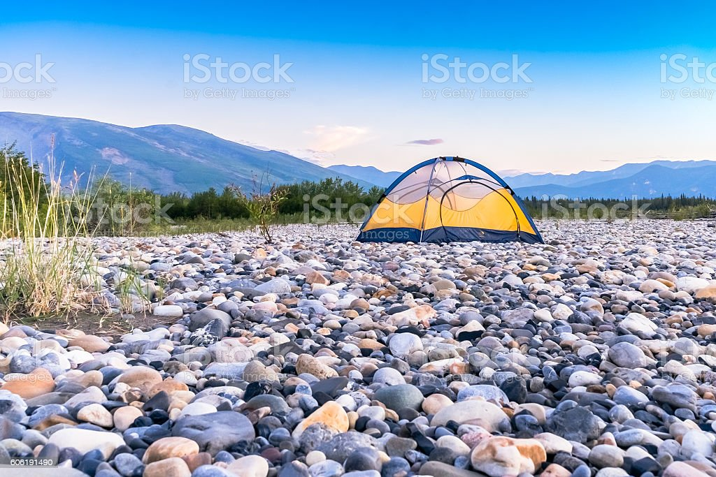 Single tent on rock riverbed stock photo
