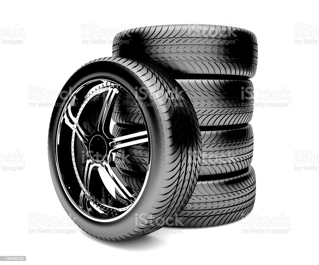 Single tire laying against a stack of four tires stock photo