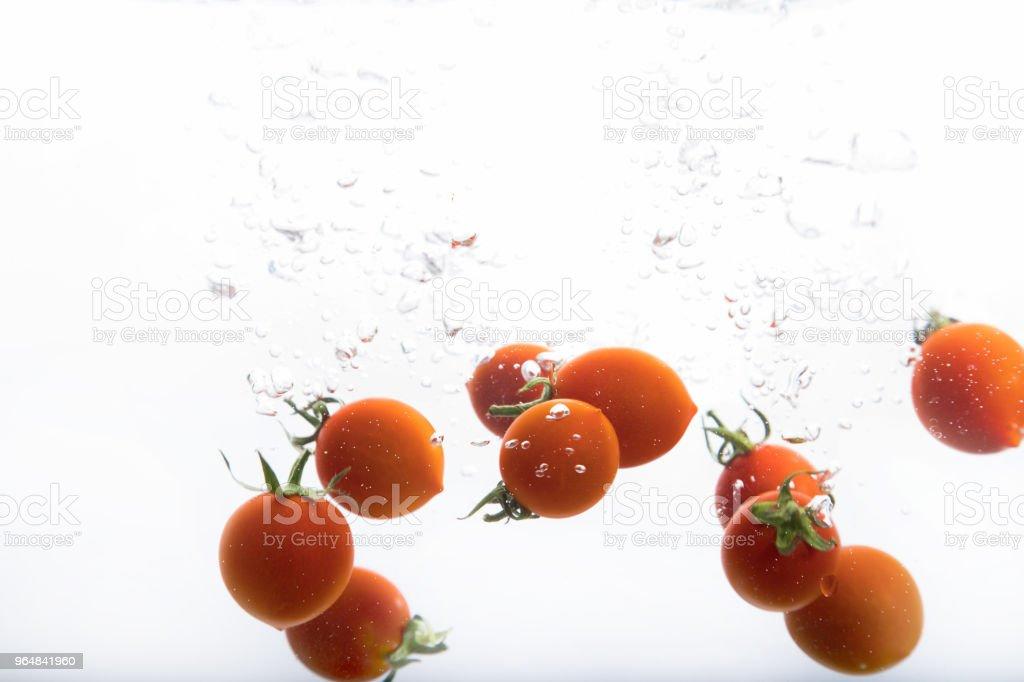 Single tomatos entering into water and splashing, isolated on white royalty-free stock photo