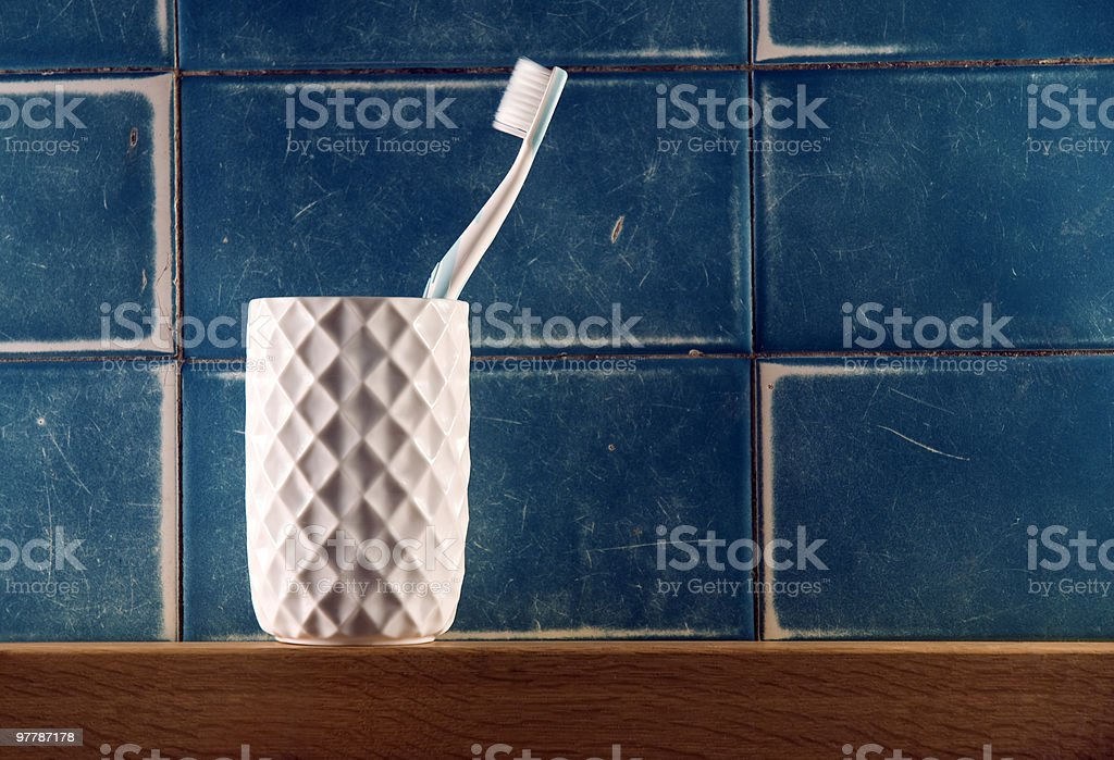 Single toothbrush in white beveled cup against blue tile stock photo