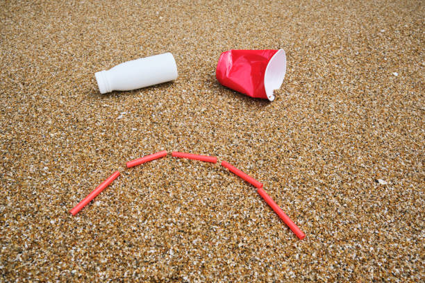 single use plastic enviromental issues, unhappy smiley face against sand with used plastic items. - trash stock photos and pictures