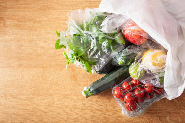 single use plastic packaging issue. fruits and vegetables in plastic bags single use plastic packaging issue. fruits and vegetables in plastic bags plastic bag stock pictures, royalty-free photos & images