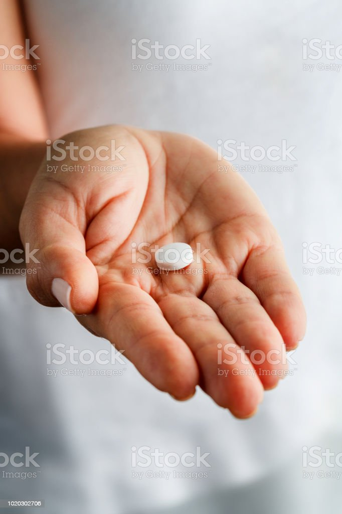 Single white aspirin pill on young woman hands stock photo