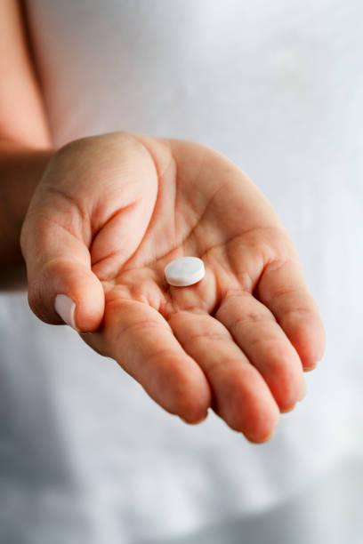 genç kadın elindeki tek beyaz aspirin hapı - aspirin stok fotoğraflar ve resimler