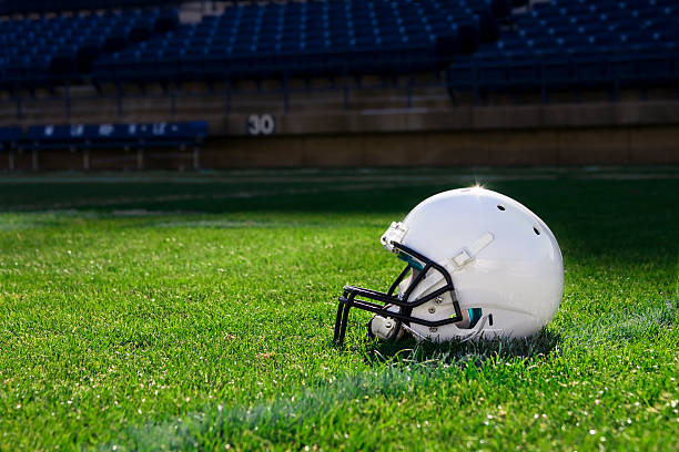 Single white football helmet on the field A football helmet rest on the field in a stadium american football uniform stock pictures, royalty-free photos & images