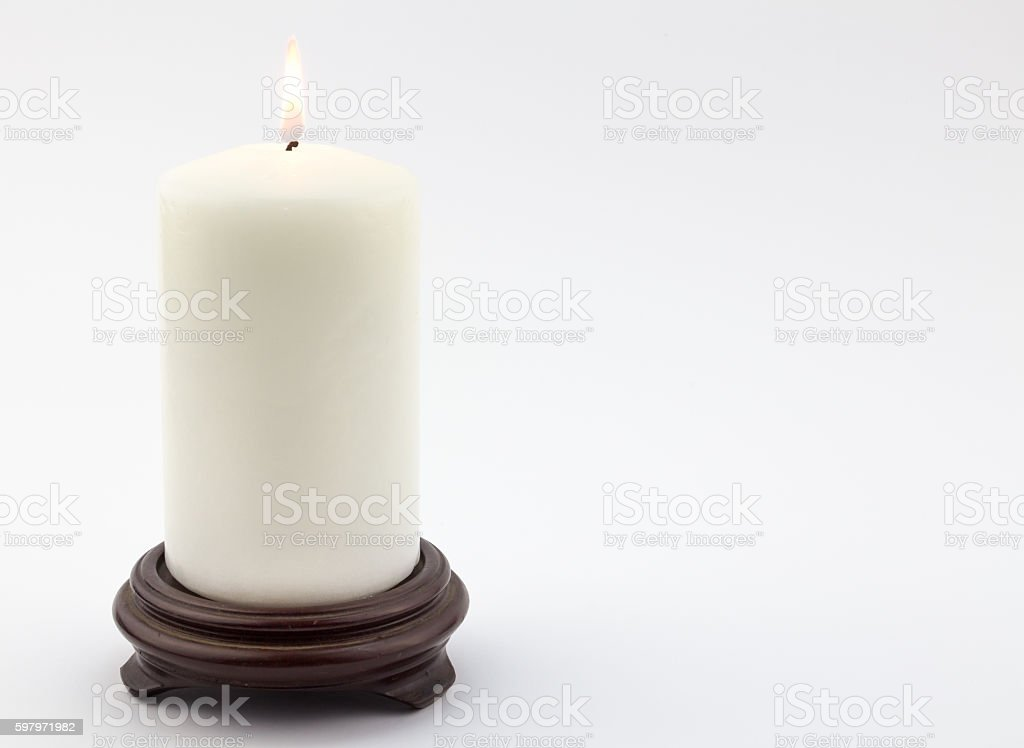 Single white lit candle on white background stock photo