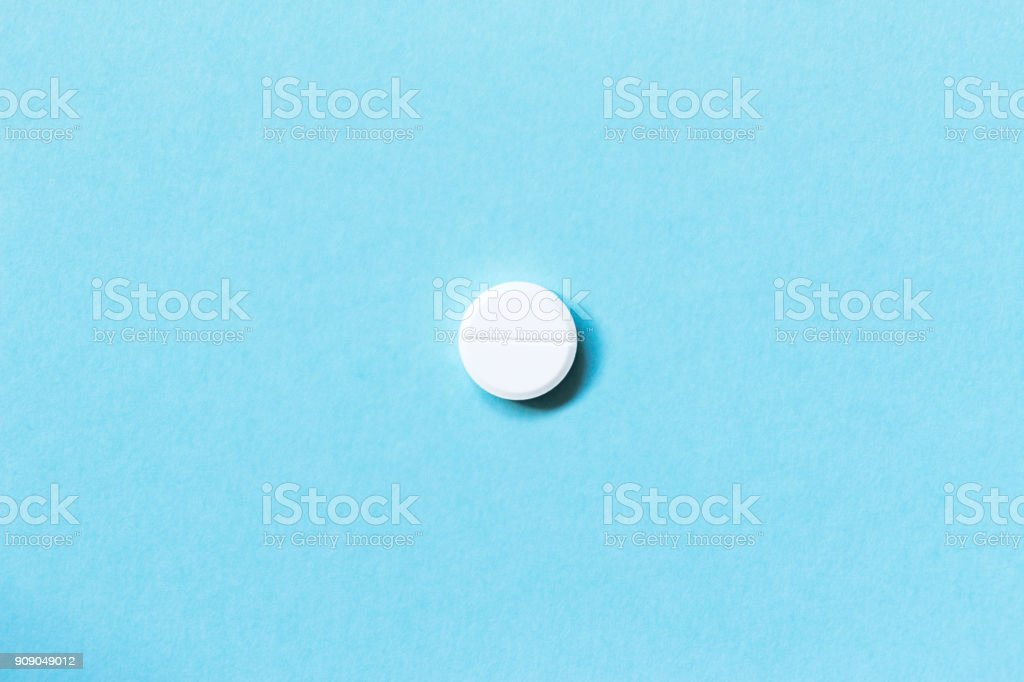 Single white pills on a blue background. Medications. Flat lay. Concept medicine stock photo