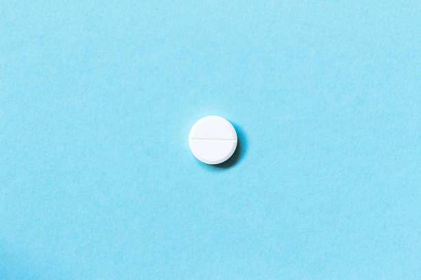 single white pills on a blue background. medications. flat lay. concept medicine - single object stock pictures, royalty-free photos & images