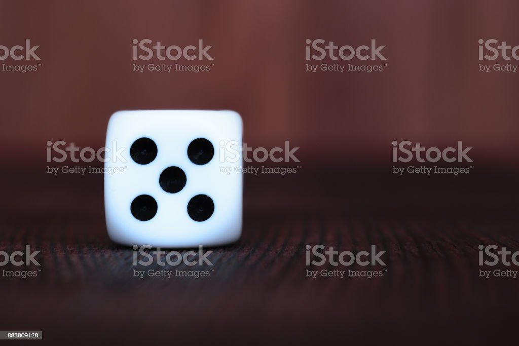 Single white plastic dice on brown wooden board background. Six side cube with black dots. Number 5 stock photo