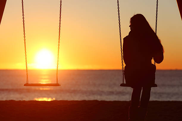 Single woman alone swinging on the beach Single woman alone swinging on the beach and looking the other seat missing a boyfriend mourning stock pictures, royalty-free photos & images