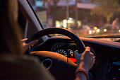 Woman holds the steering wheel of a car with two hands. Driving at night, commuting with an empty fuel tank