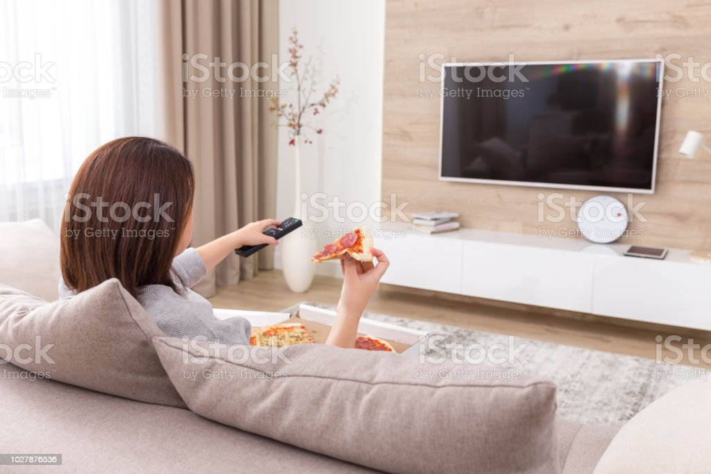 Single woman eating pizza and watching tv stock photo