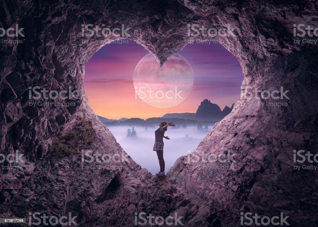 Mujer sola en la cueva de la forma del corazón hacia el paisaje idílico - foto de stock
