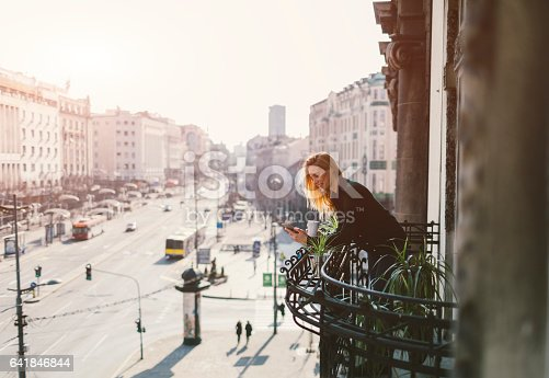 Single woman drinking coffee and using her smart phone on hotel balcony