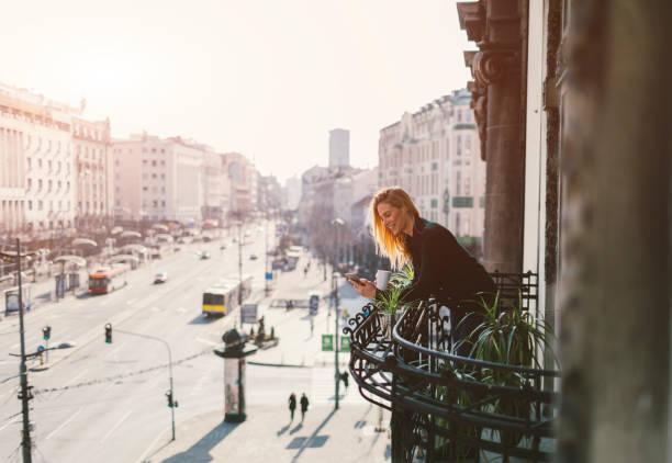 single-frau auf hotelbalkon - städtetrip stock-fotos und bilder