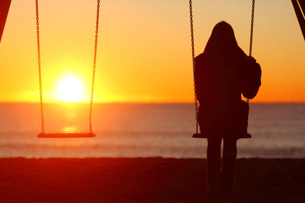 Single woman sitting on a swing contemplating sunset Single woman sitting on a swing contemplating sunset mourning stock pictures, royalty-free photos & images