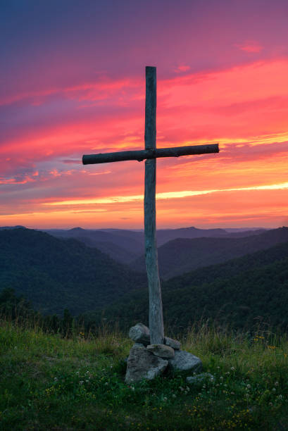 Single wooden cross against sunset stock photo