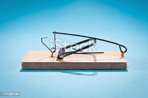 Single wooden mousetrap isolated on blue, side view, studio shot.
