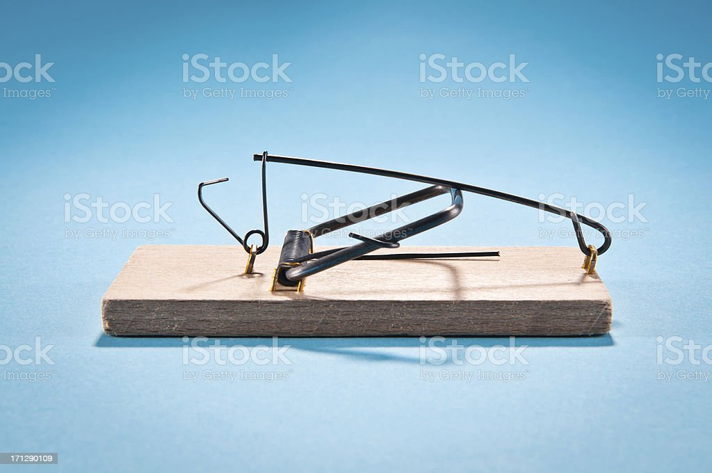 Single wooden mousetrap isolated on blue, side view, studio shot stock photo