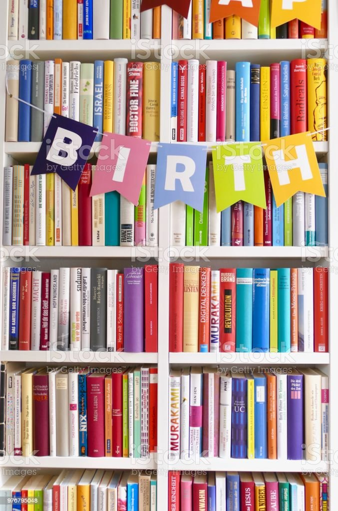 Single word birth letters hanging on bookshelf in library