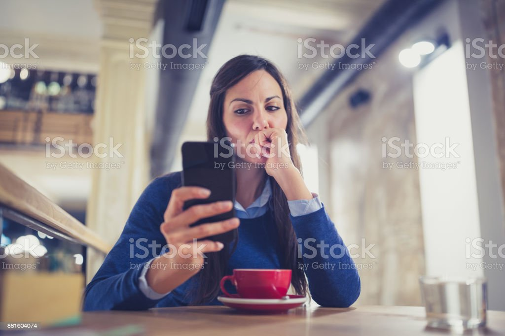 Single. Worried young woman using smart phone in cafe stock photo