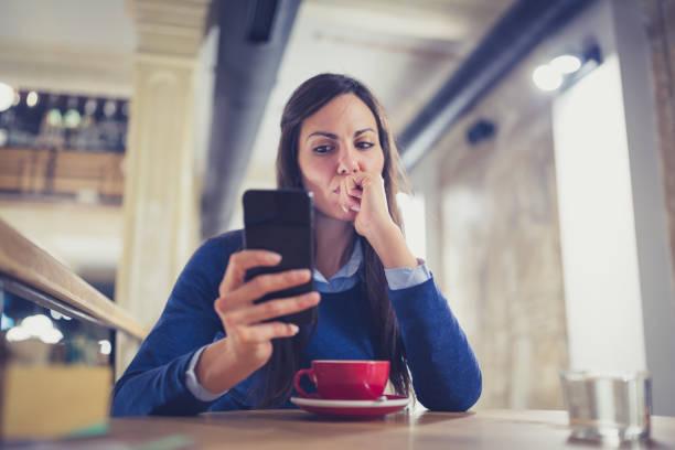 één. bezorgd jonge vrouw met behulp van slimme telefoon in café - achterdocht stockfoto's en -beelden